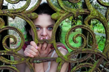 angst: Scared woman trapped or locked behind an iron gate with moss and corrosion Stock Photo