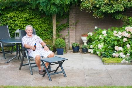 晴れた日に彼の家の裏庭でビールを楽しむシニア 写真素材