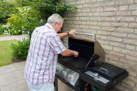 Senior man cleaning barbecue in his back garden Stock Photo - 19352327