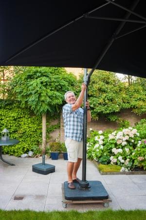 Senior man setting up beach parasol in his garden on a sunny day Stock Photo - 19352296