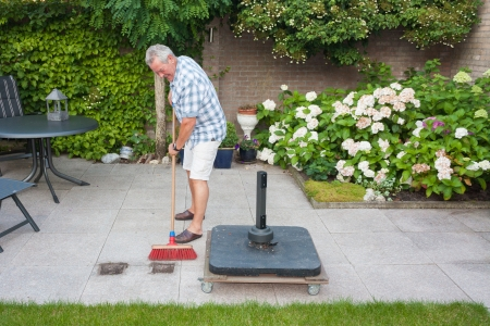 brooming: Senior man sweeping back garden on a sunny day
