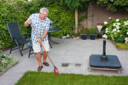 Senior man sweeping back garden on a sunny day