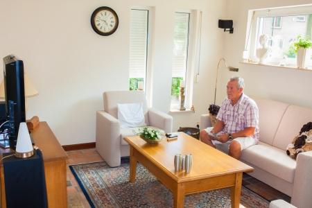 Senior man tv te kijken in de moderne lichte woonkamer Stockfoto