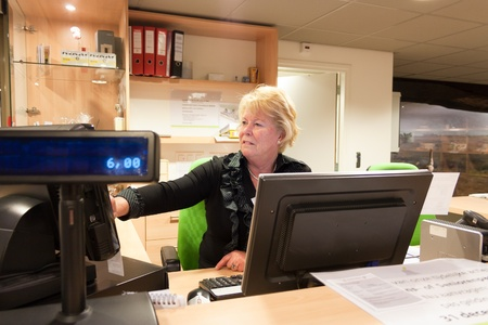 cash register: Senior volunteer female cashier at work at the museum front desk