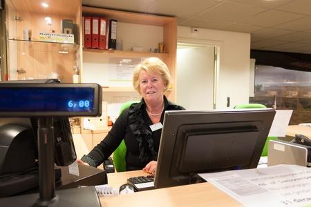 Oudere vrijwillige vrouwelijke kassier op het werk zit in het museum receptie