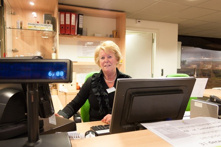 Senior volunteer female cashier at work sitting at the museum front desk