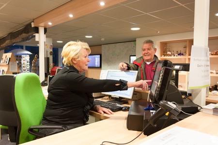 Senior female volunteer cashier selling museum ticket to Senior man at front desk Banque d'images
