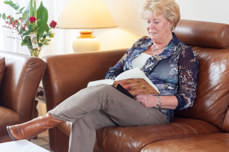 reading lamp: Senior woman sitting on brown leather couch in living room reading a book