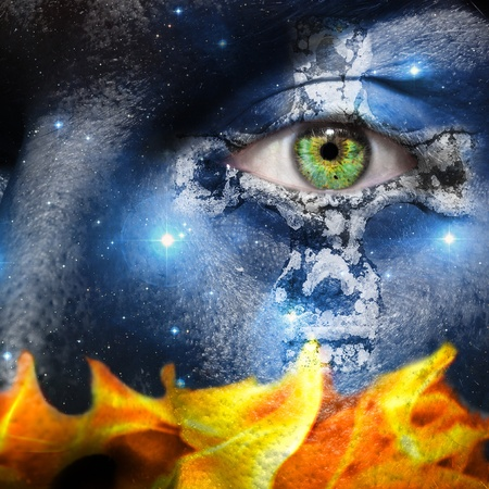 centering: Face overlay of the seven sisters constellation with a Celtic cross centering around the green eye with a base of fire flames Stock Photo