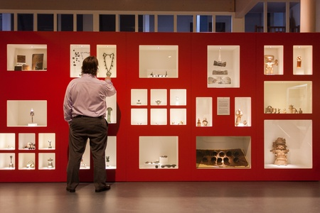 Visitor in a museum looking at relics in a display