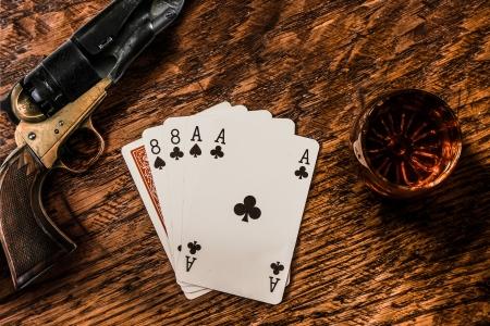 Wild Bill Dead Mans Hand met een whiskey schot en een revolver Stockfoto