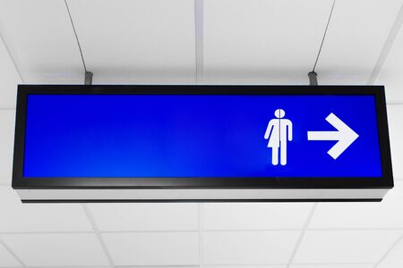 Blue public sign showing unisex toilet directions
