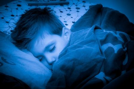 素敵な温かみのある居心地の良いベッドで寝ている少年 写真素材