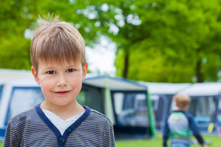 Little boy on camping site with caravan tent in background photo