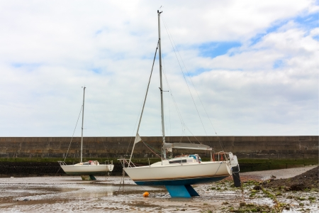keel: Dried out tidal harbour with sail boats resting on the keel