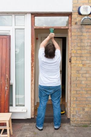 Man sanding down the front door Stock Photo - 20108576