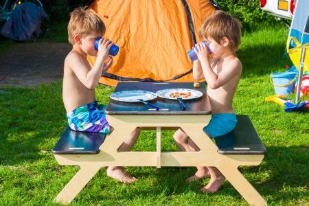 Twee broers zitten aan een kleine tafel bankje eten en drinken Stockfoto