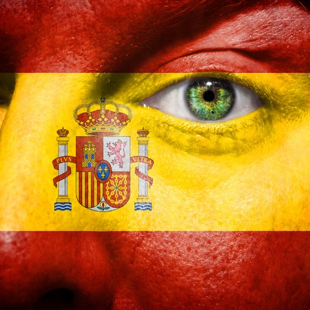 follower: Spanish flag painted on mans face to support his country Spain Stock Photo