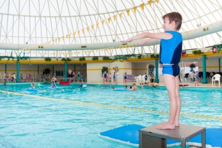 青を身に着けているプールで少年の人生ベスト ダイビングを取る準備ができて 写真素材