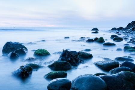 sunup: Bray Head rocks in the Irish Sea early morning cool blue long exposure image