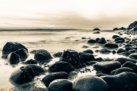 sunup: Bray Head rocks in the Irish Sea in sepia long exposure image Stock Photo