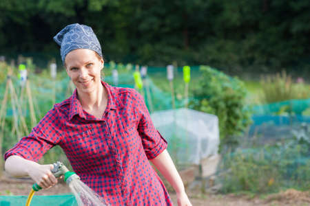 Smiling woman using a garden hose nozzle to water the allotment Stock Photo - 21643701