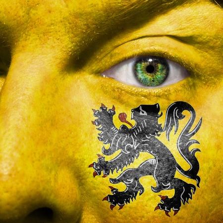flemish region: Flemish flag painted on a mans face