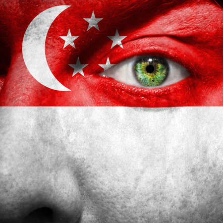 singaporean flag: Singapore flag painted on a man Editorial