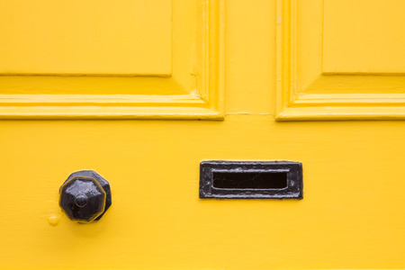front door: Detail of a yellow front door with black knob and letter box Stock Photo