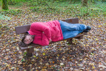 slacker: Man sleeping on a bench in a forest in autumn