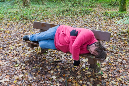 slacker: Sleeping man on a bench in a forest Stock Photo