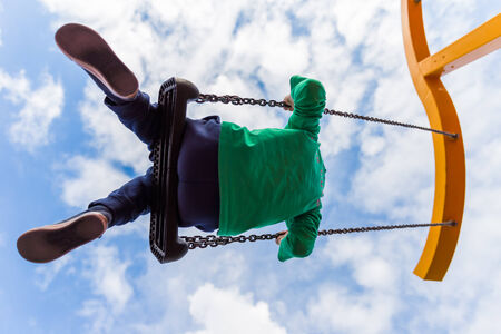 Young boy having fun on a swing against a blue clouded sky