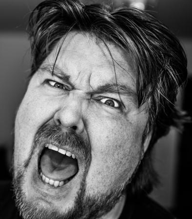 Hombre furioso gritando fren�ticamente con una mirada intensa en sus ojos de la frustraci�n en monocromo photo