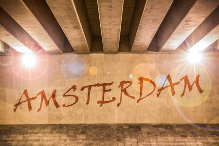 The word Amsterdam painted as graffiti on the support column of an overpass photo