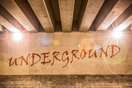 sprayed: The word underground painted as graffiti on the support column of an overpass