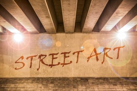 underpass: The words street art painted as graffiti on the support column of an overpass