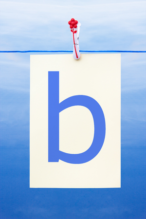 Seamless washing line with paper against a blue sky showing the letter b
