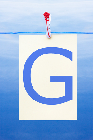 Seamless washing line with paper against a blue sky showing the letter G