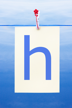 Seamless washing line with paper against a blue sky showing the letter h