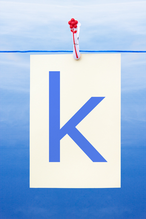 Seamless washing line with paper against a blue sky showing the letter k
