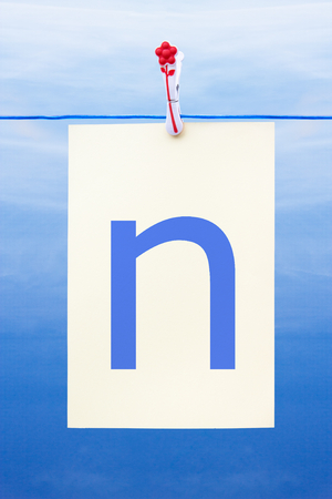 Seamless washing line with paper against a blue sky showing the letter n