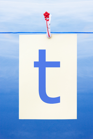 Seamless washing line with paper against a blue sky showing the letter t