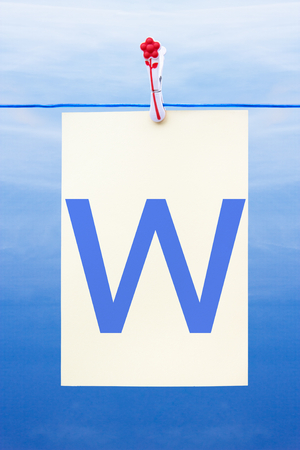 Seamless washing line with paper against a blue sky showing the letter w Stock Photo