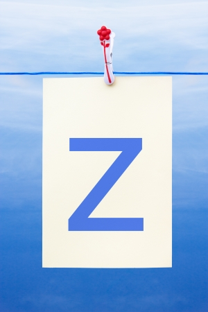 Seamless washing line with paper against a blue sky showing the letter z