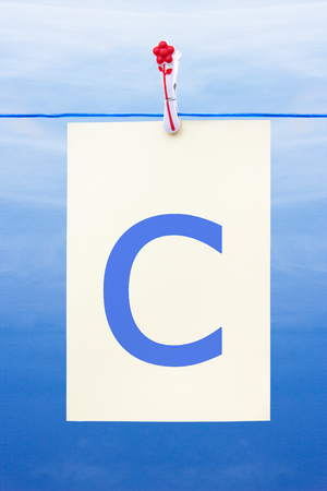 Seamless washing line with paper against a blue sky showing the letter c