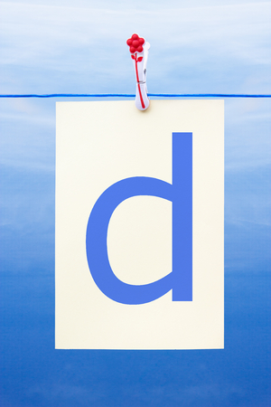 Seamless washing line with paper against a blue sky showing the letter d Stock Photo