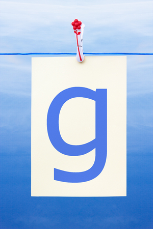 Seamless washing line with paper against a blue sky showing the letter g Stock Photo