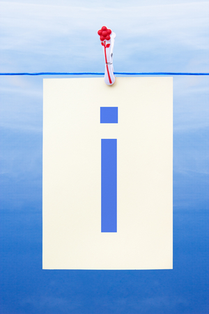 Seamless washing line with paper against a blue sky showing the letter i