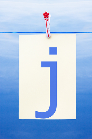 Seamless washing line with paper against a blue sky showing the letter j