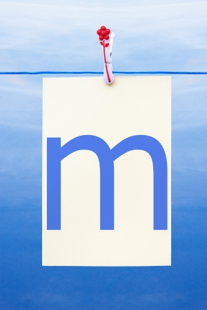 Seamless washing line with paper against a blue sky showing the letter m photo